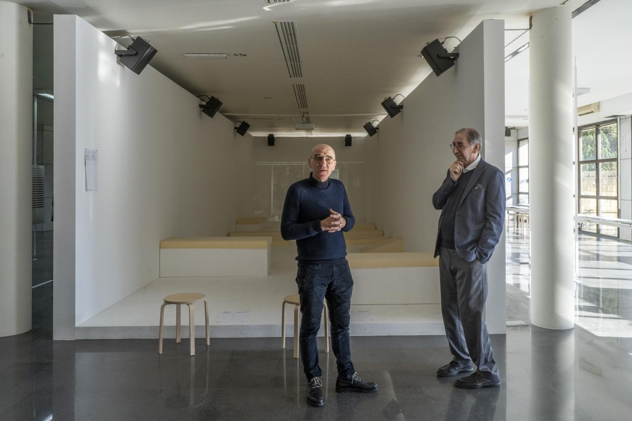 Two men stand in a large bright room.