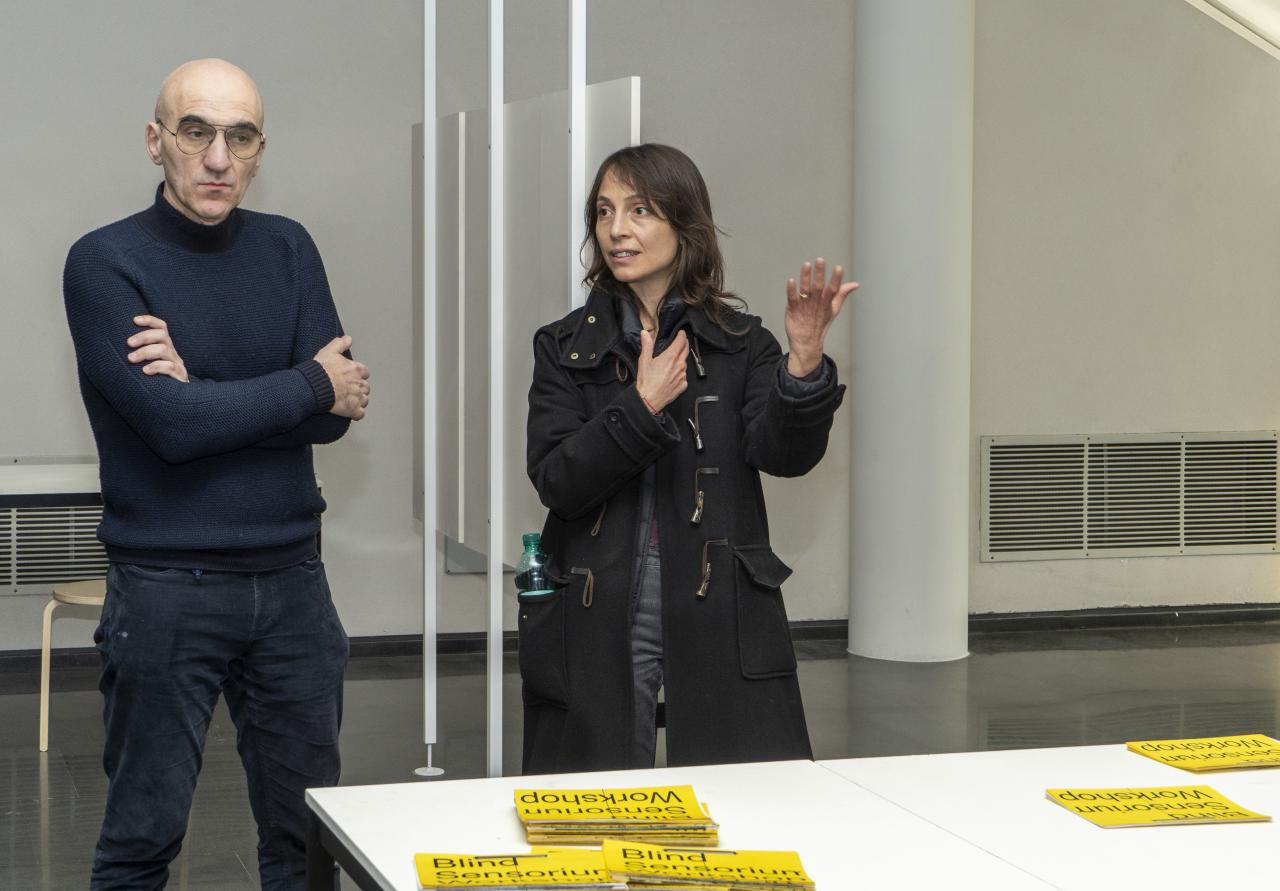 Two people stand in front of a table with yellow and black cards.