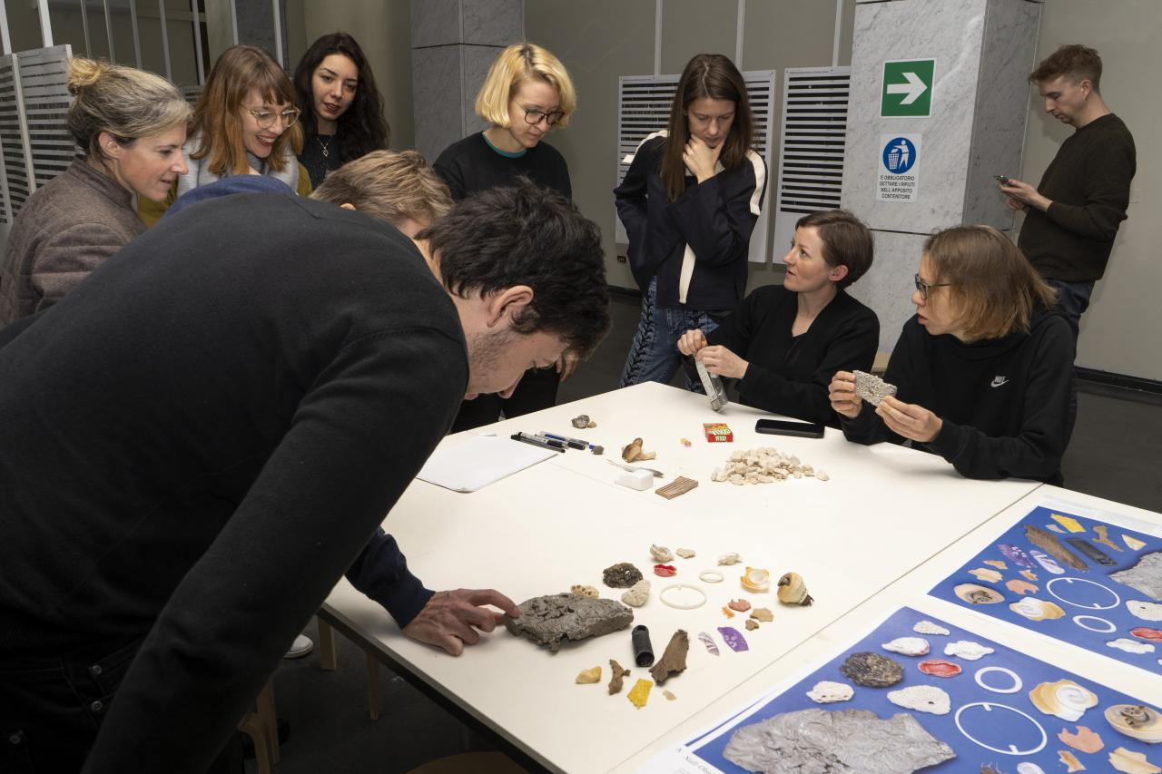 A group of people in front of a table with different materials.