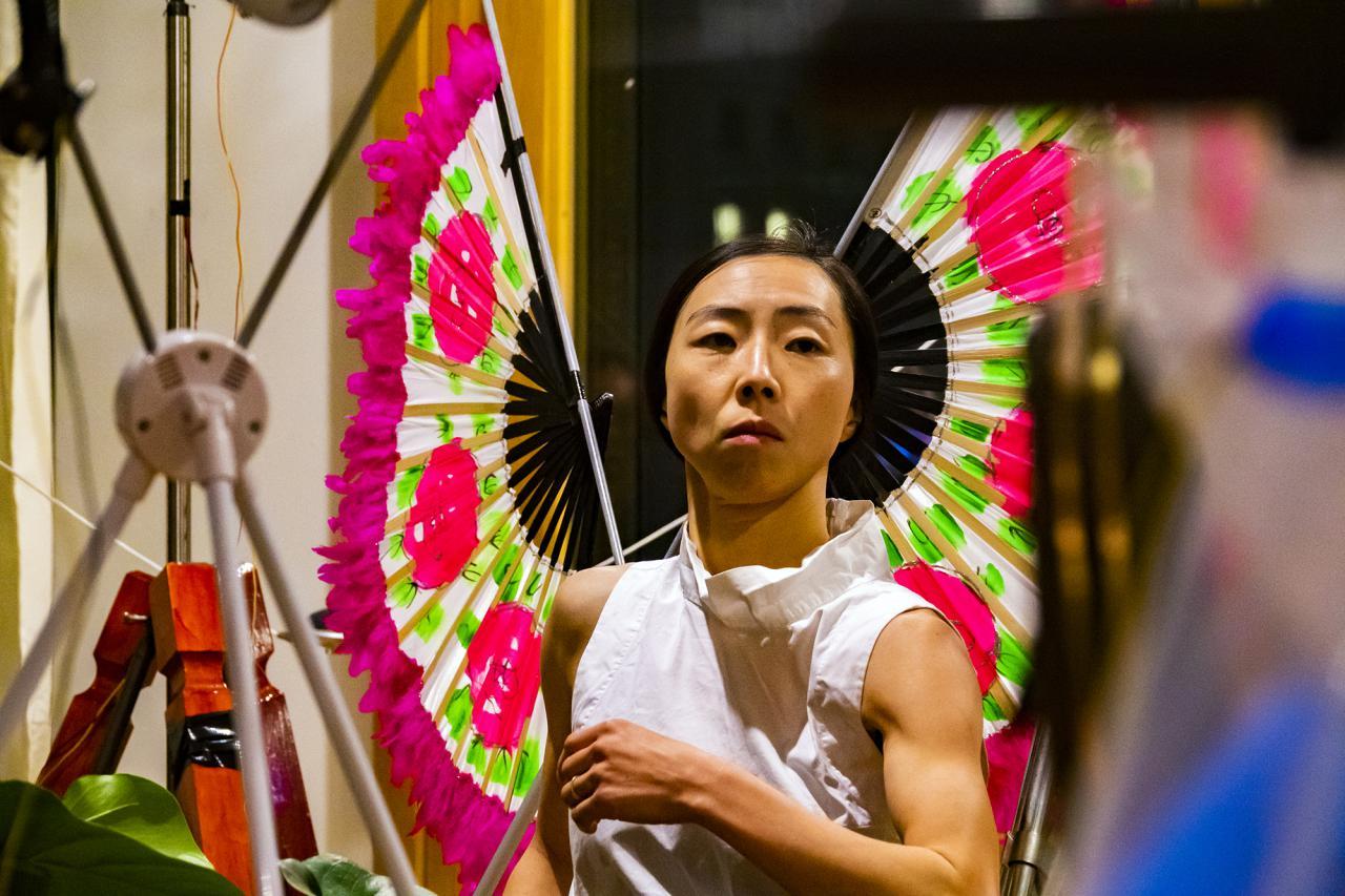 Das Foto zeigt den Oberköper und Kopf einer koreanischen Performerin die zwei pink/hellgrün farbige Fächer aus Holz als Flügel trägt.