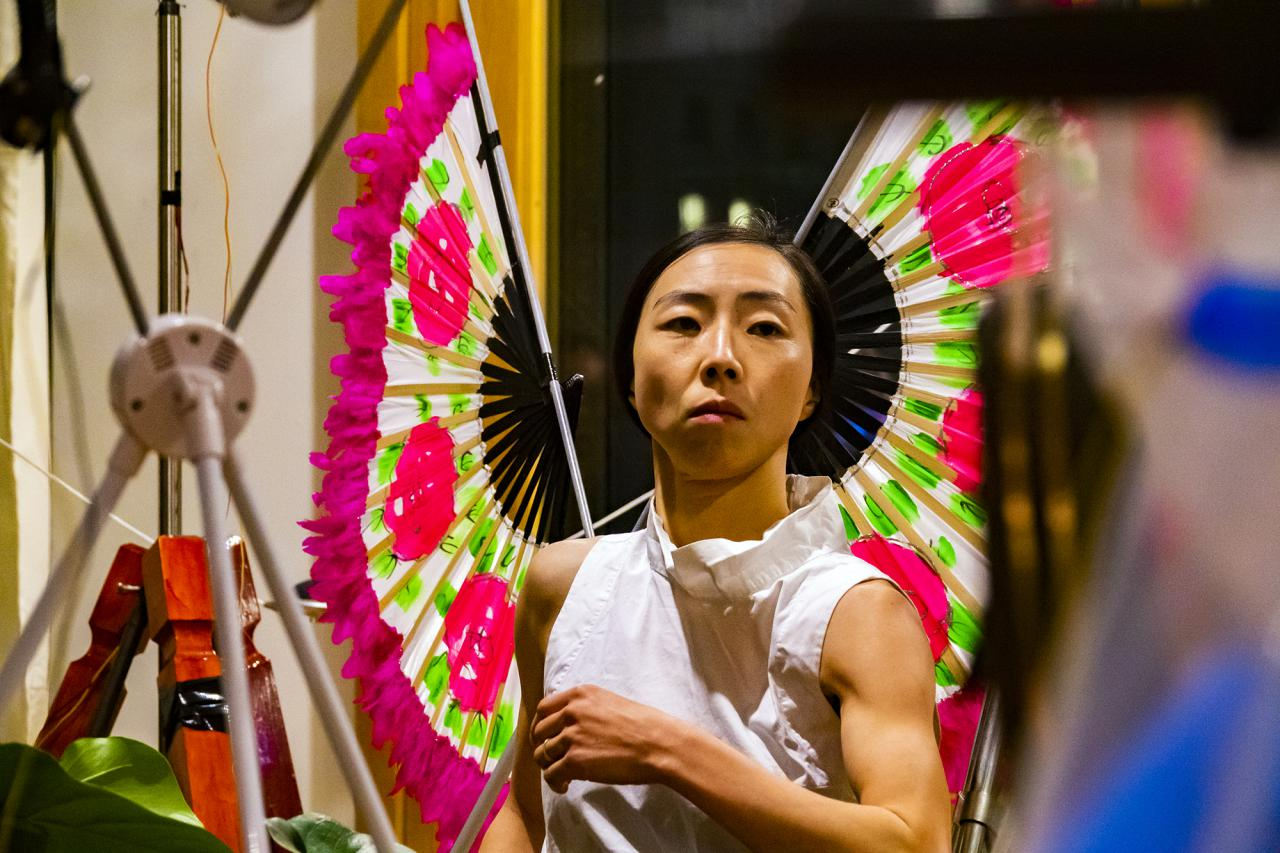 The photo shows the upper body and head of a Korean performer wearing two pink/light green coloured wooden fans as wings.