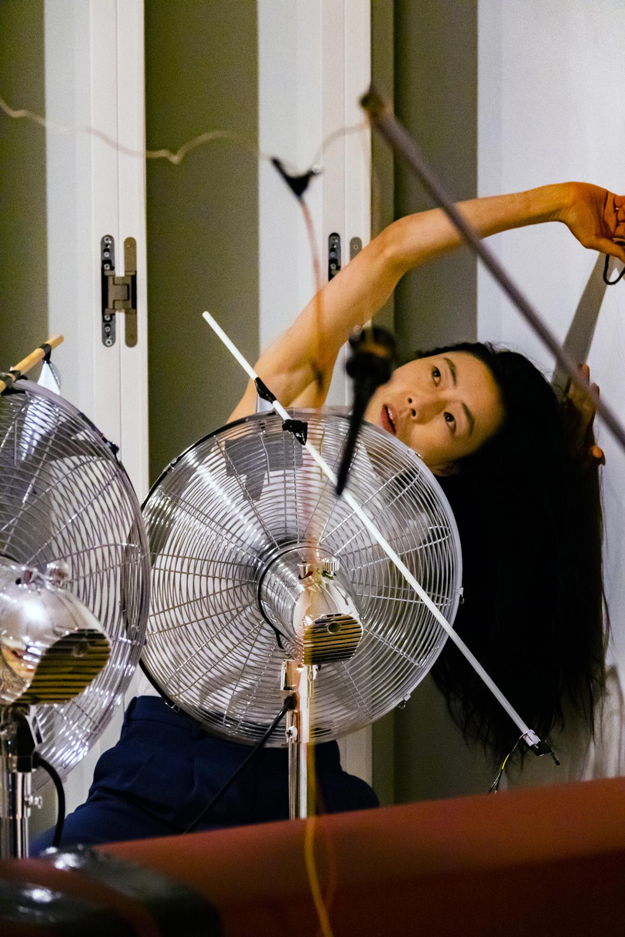 The photo shows a Korean performer bent to the left stretching her arm over her head while a large silver fan is standing in front of her.