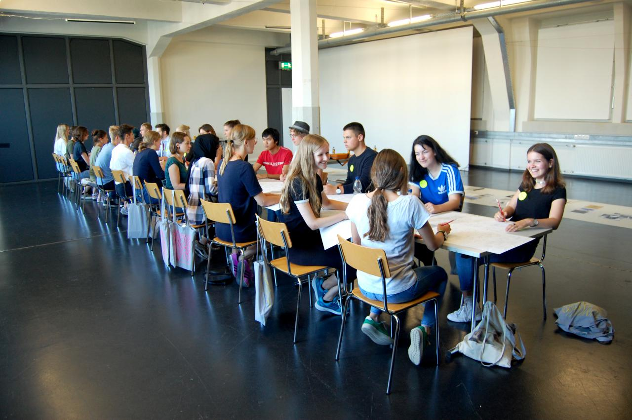 Viele junge Schüler sitzen an einem Tisch im Rahmen einer Veranstaltung der Kulturakademie.