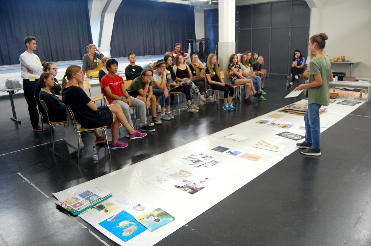 Eine Schülerin stellt einer Gruppe von Schülern verschiedene Bildwerke vor im Rahmen einer Veranstaltung der Kulturakademie.