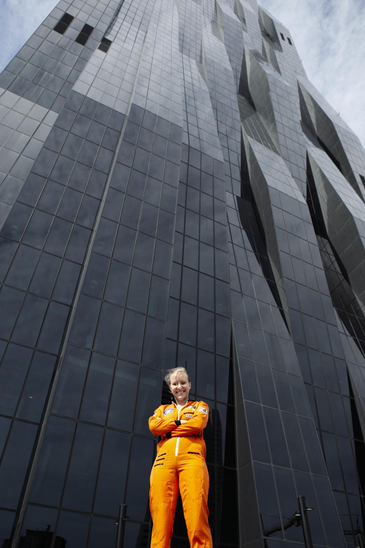 Raphaela Edelbauer im orangen Space-Suit vor einem verglasten Hochhaus.
