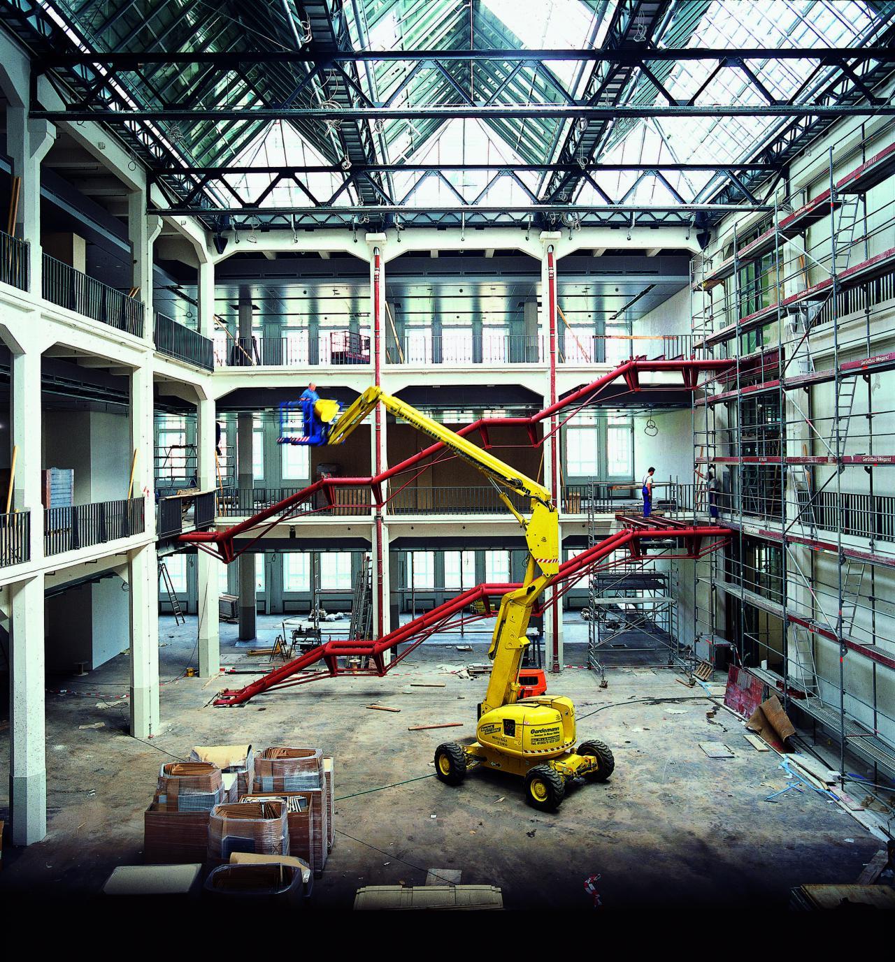 Das Foto zeigt eine historische Ansicht des Umbaus des alten MNK Hallenbaus. Ein imposanter großer gelber Bagger steht mitten in der Halle während im Hintergrund die Rohkonstruktion der zukünftigen Treppen des Ausstellungsraumes in rot hell leuchten.