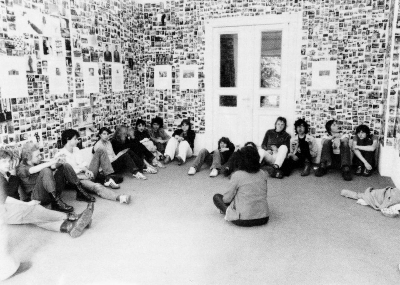 Jugendliche sitzen in einem Raum, dessen Wände mit Fotografien bedeckt ist.