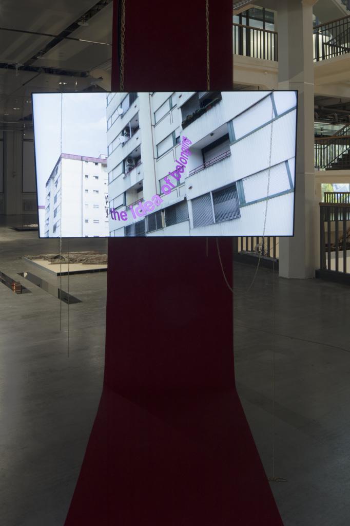 Ein Bildschirm zeigt eine Hochhausfront, darauf der Schriftzug »the idea of belonging«
