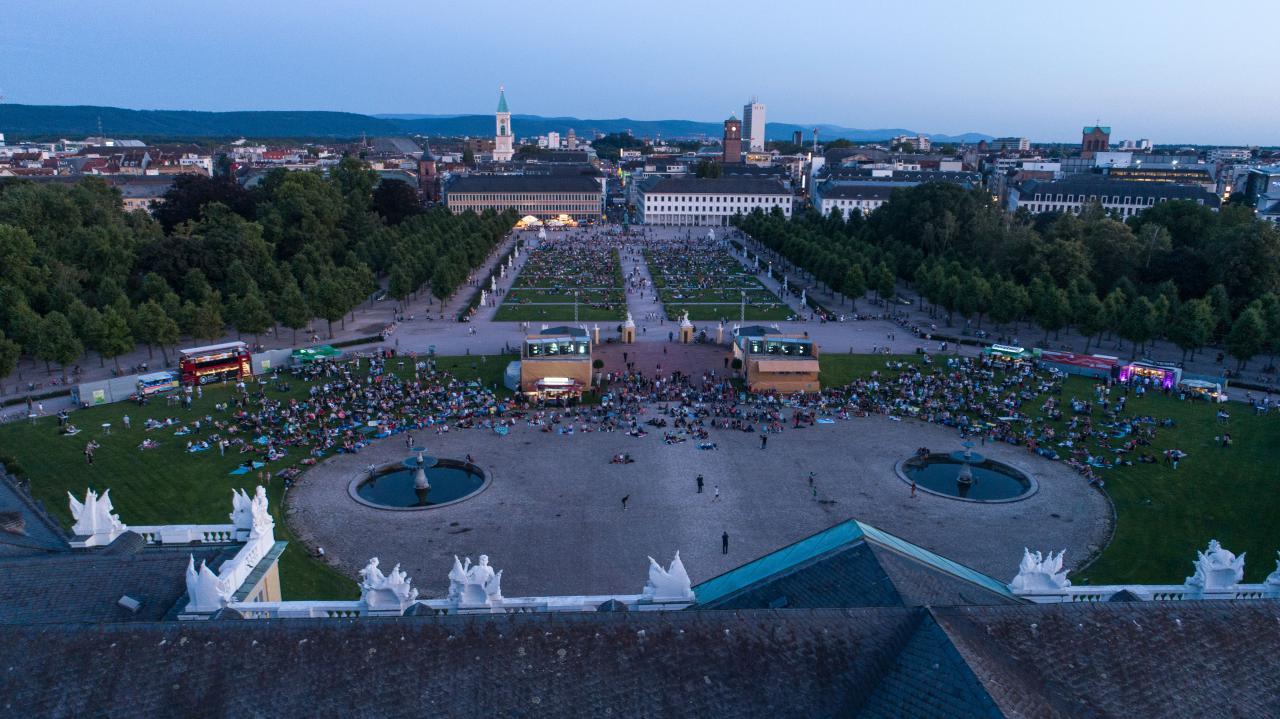 Das Foto zeigt einen Überblick auf die BesucherInnen der Premiere der Schlosslichtspiele 2019. Das Foto wurde mit einer Drohne oberhalb des Schlosses aufgenommen und zeigt eine große Menschenmasse auf der Grünwiese vor dem Karlsruher Schloss.
