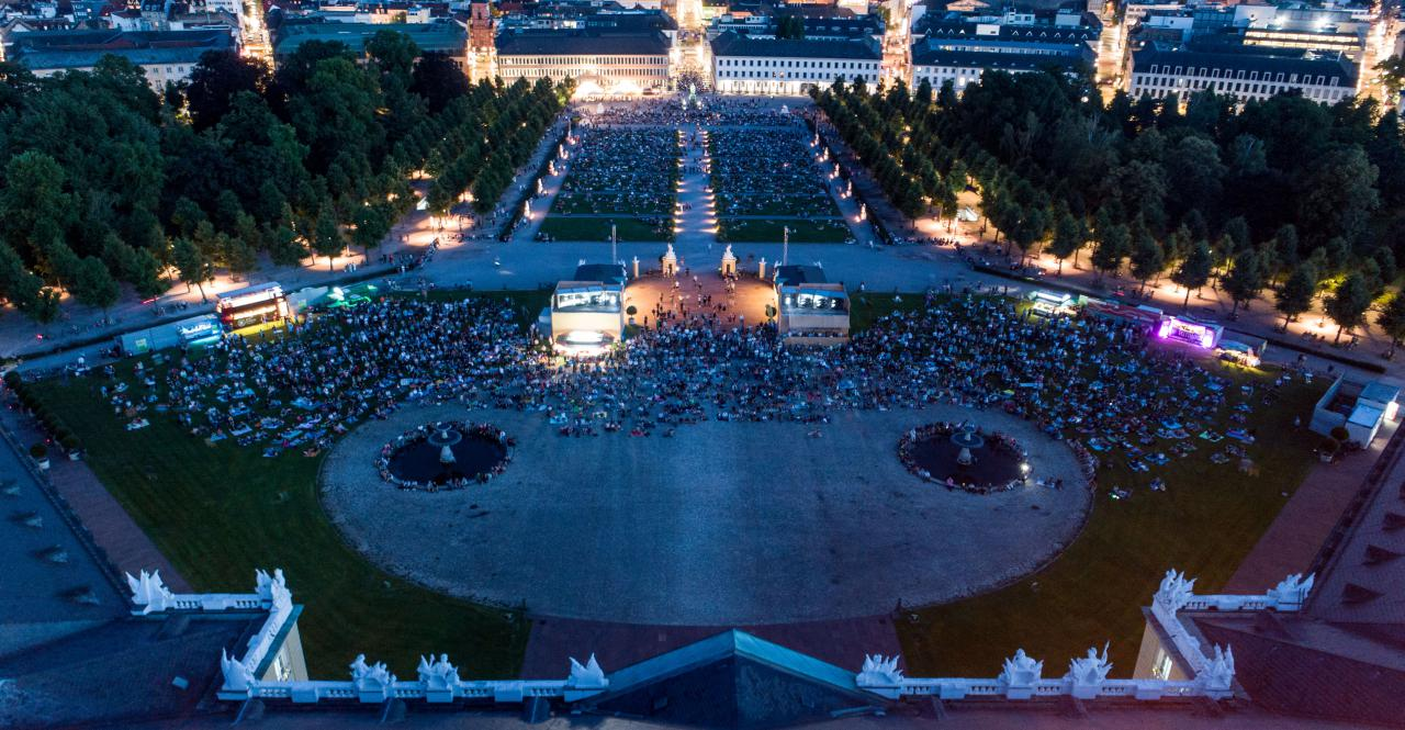 The photo shows an overview of the visitors of the premiere of the Schlosslichtspiele 2019. The photo was taken with a drone above the castle and shows a large crowd of people on the green meadow in front of Karlsruhe Castle.