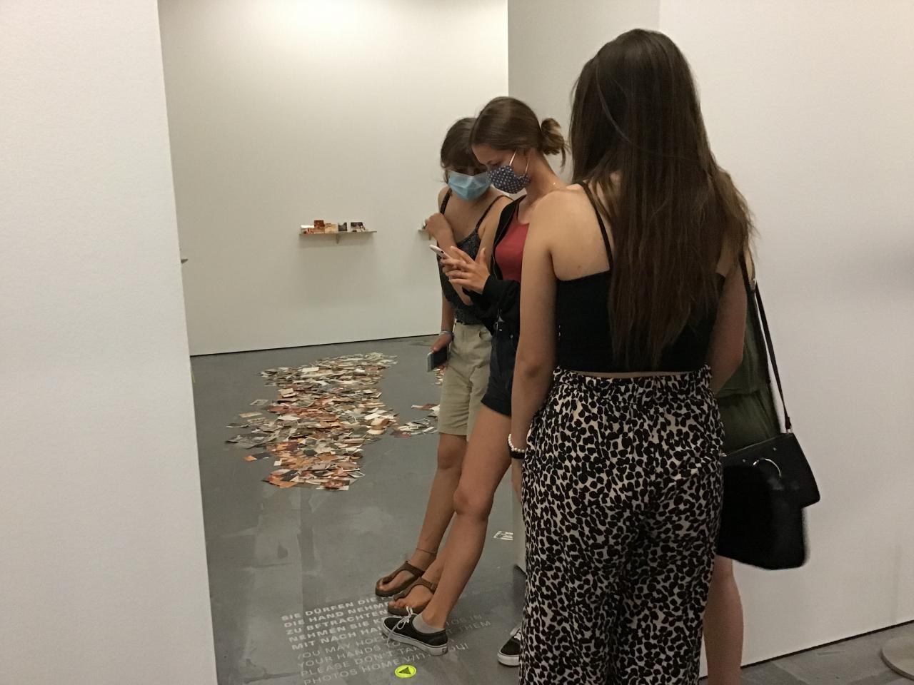 You can see three girls who have put their feet on a text on the floor and take a photo of it.