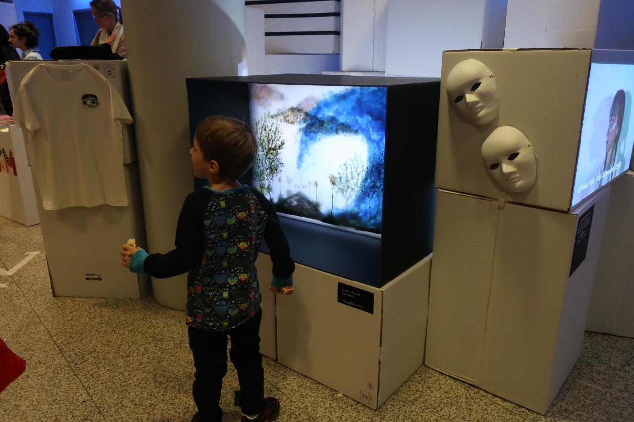 Ein kleiner Junge steht vor einem Fernseher im Rahmen einer Veranstaltung der Kulturakademie.