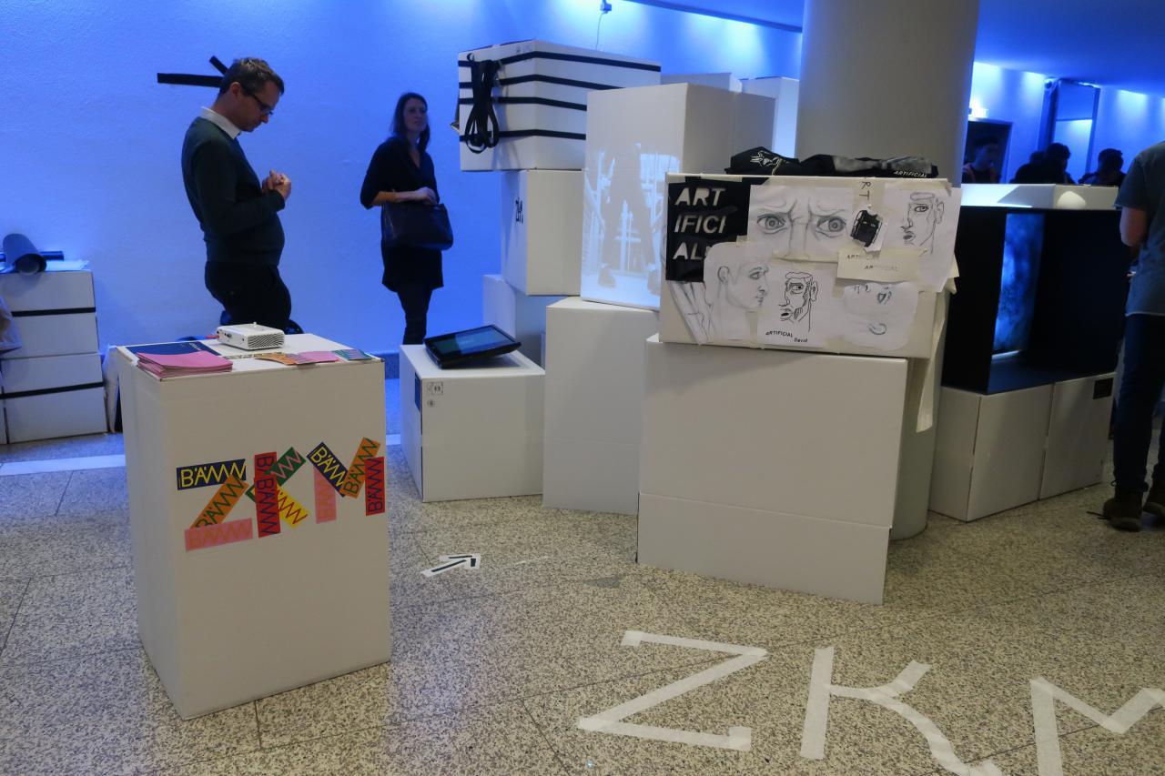Zu sehen ist ein Raum mit Menschen und verschieden Zeichnungen auf aufeinander gestapelten Kartons im Rahmen einer Veranstaltung der Kulturakademie.