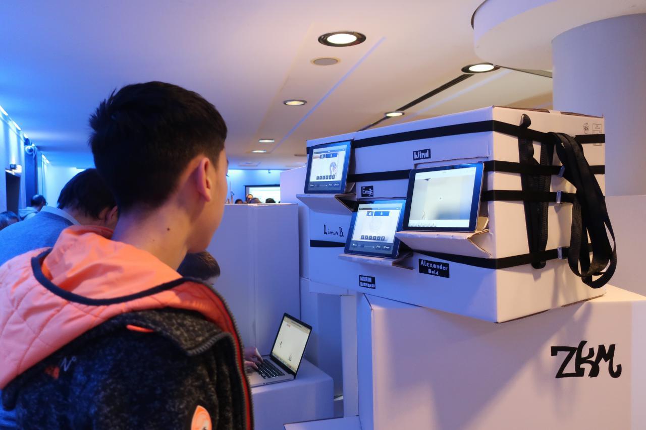 Zu sehen ist ein Junge vor drei aufgestellten iPads im Rahmen einer Veranstaltung der Kulturakademie.