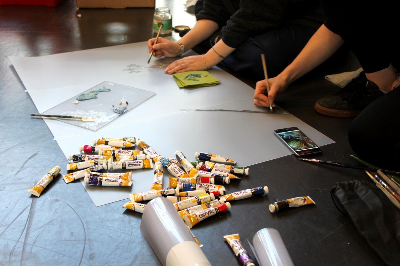 Zu sehen sind viele malende Hände auf Papier und verschiedene Farbtuben im Rahmen einer Veranstaltung der Kulturakademie.