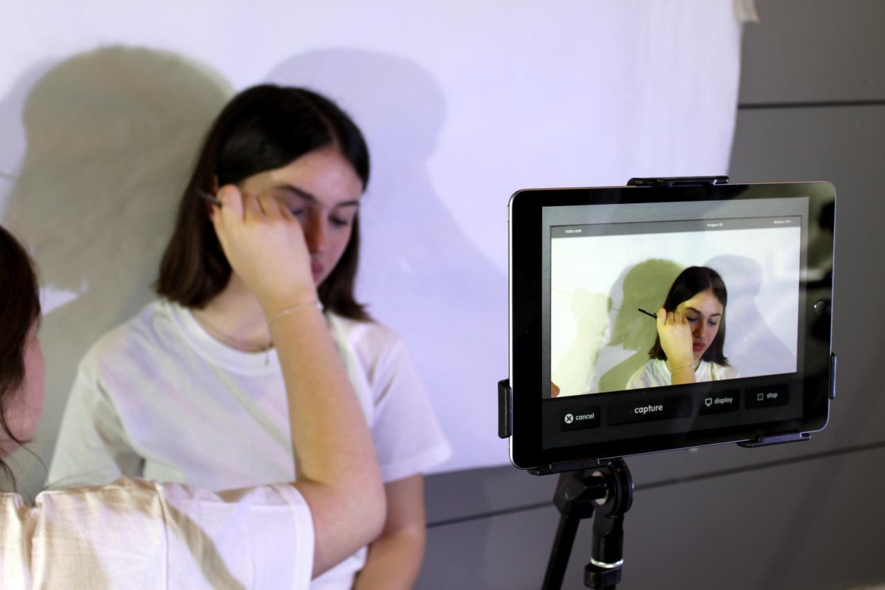 Zu sehen ist ein Mädchen, das vor einer Kamera geschminkt wird im Rahmen einer Veranstaltung der Kulturakademie.