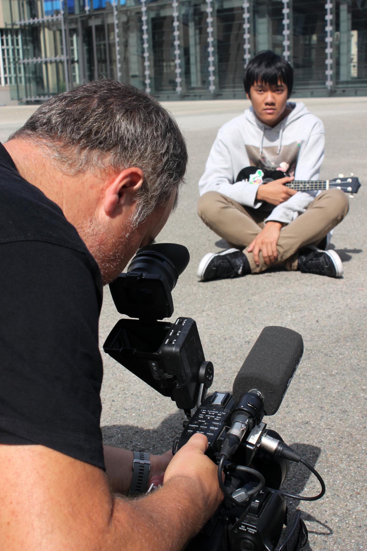 Ein Fotograf macht ein Bild von einem Schüler mit einer Gitarre im Rahmen einer Veranstaltung der Kulturakademie.