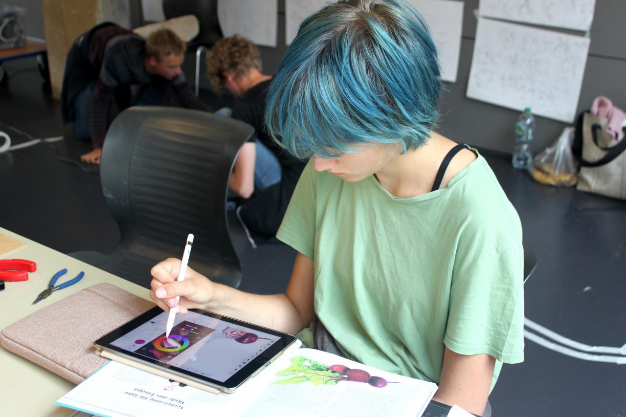 Eine Schülerin malt auf einem iPad im Rahmen einer Veranstaltung der Kulturakademie.