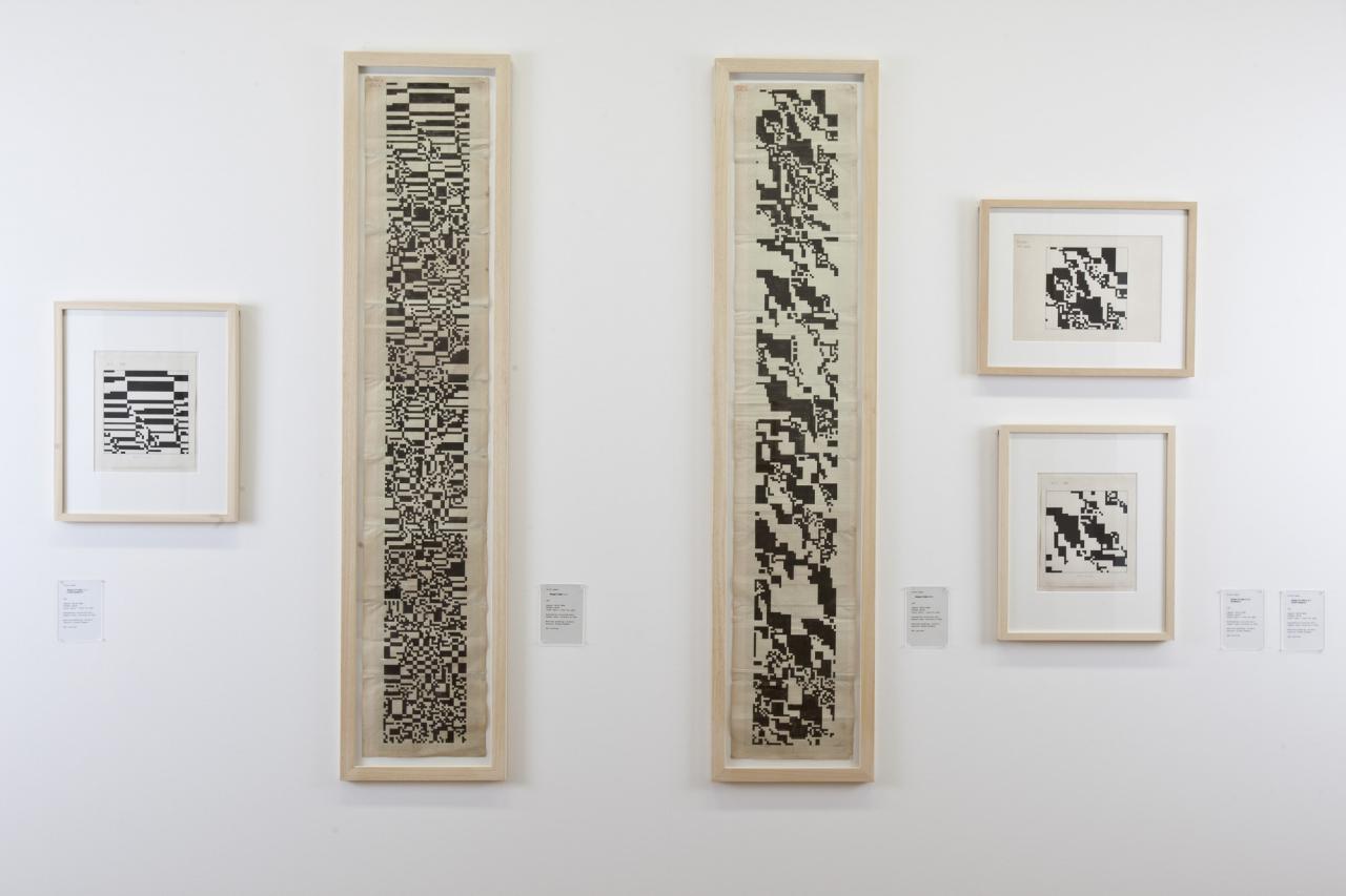 Blick auf eine weiße Wand mit sechs Bildern, mit abstrakten, schwarz-weißen Mustern.