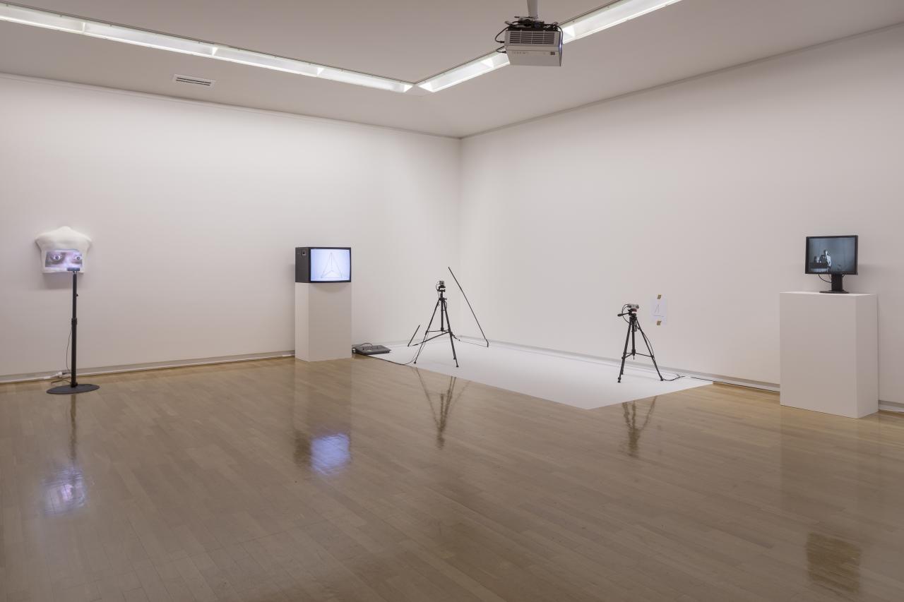 Zu sehen ist die Ecke eines Raumes, an der vier Objekte stehen. Zu erkennen sind zwei Bildschirme und zwei Stative, welche im großen Abstand zueinander stehen.