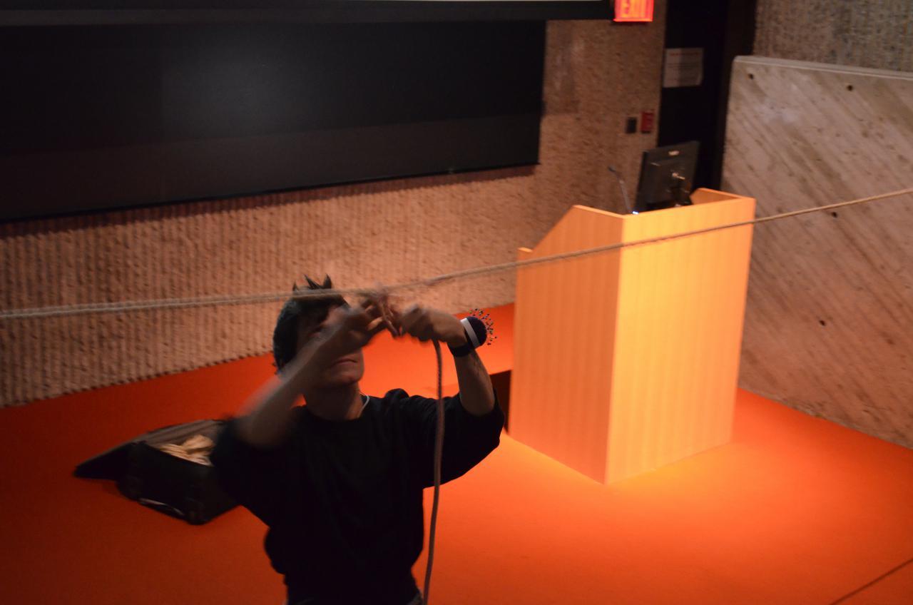 Das Foto zeigt eine Performerin im Vordergrund die an einem hängenden Seil ein weiteres befästigt. Sie trägt ein Nadelkissen um ihr linkes Handgelenk. Die schwarz gekleidete Person steht schräg vor dem Rednerpult auf dem orangenen Teppich.