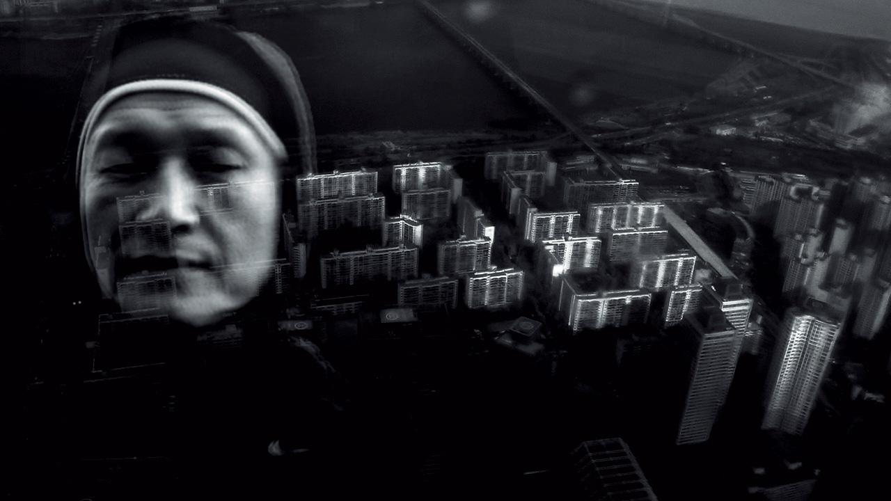 The black and white collage shows a nun in front of a bird's eye view on skyscrapers.