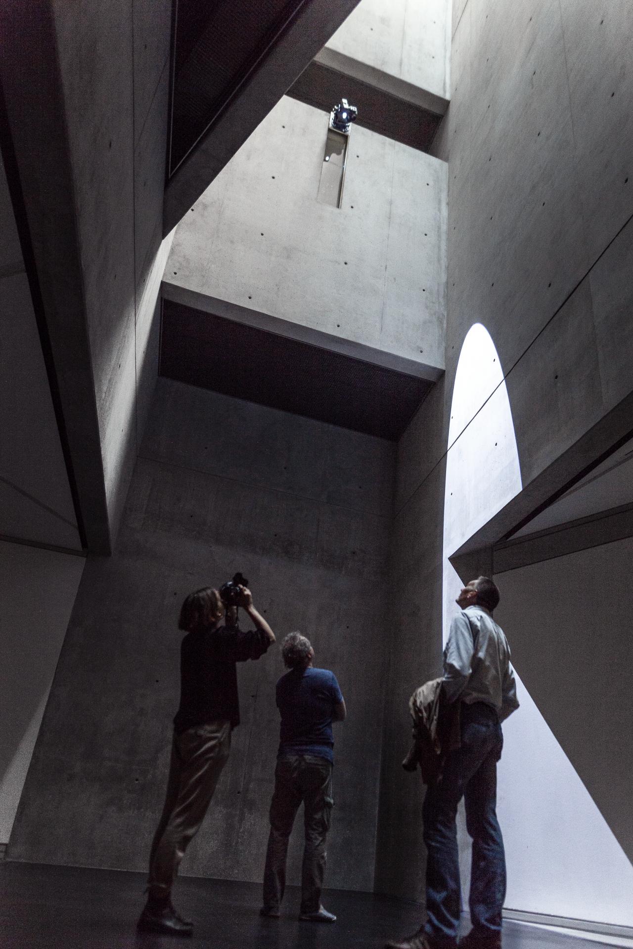 Zu sehen sind 3 Personen in einem hohen Raum mit Betonwänden, in den das Sonnenlicht von oben reinstrahlt