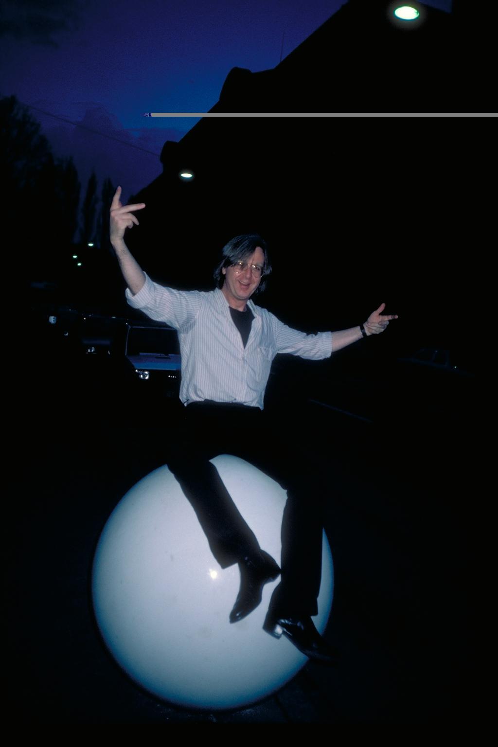 Fotografie von Gerhard Johann Lischka, auf einer großen weißen Kugel sitzend