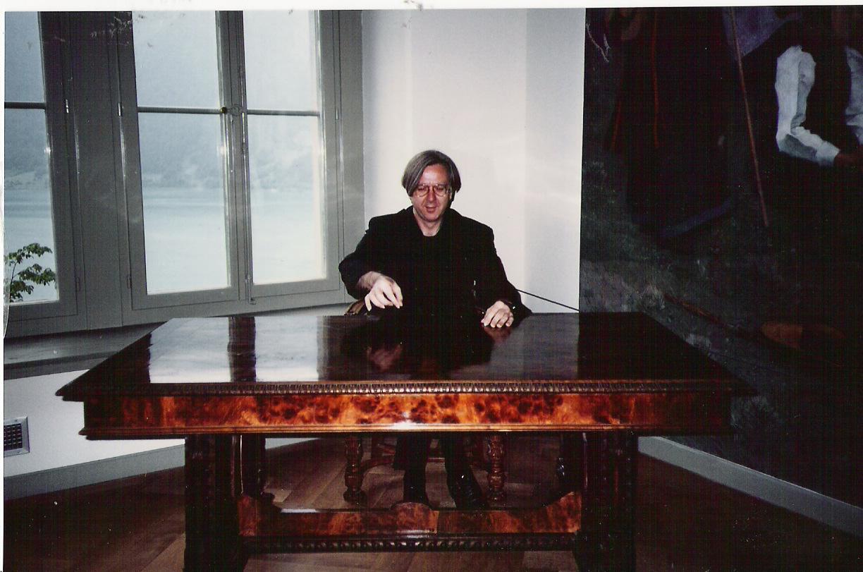 Fotografie von Gerhard Johann Lischka, hinter einem großen, schweren Schreibtisch sitzend