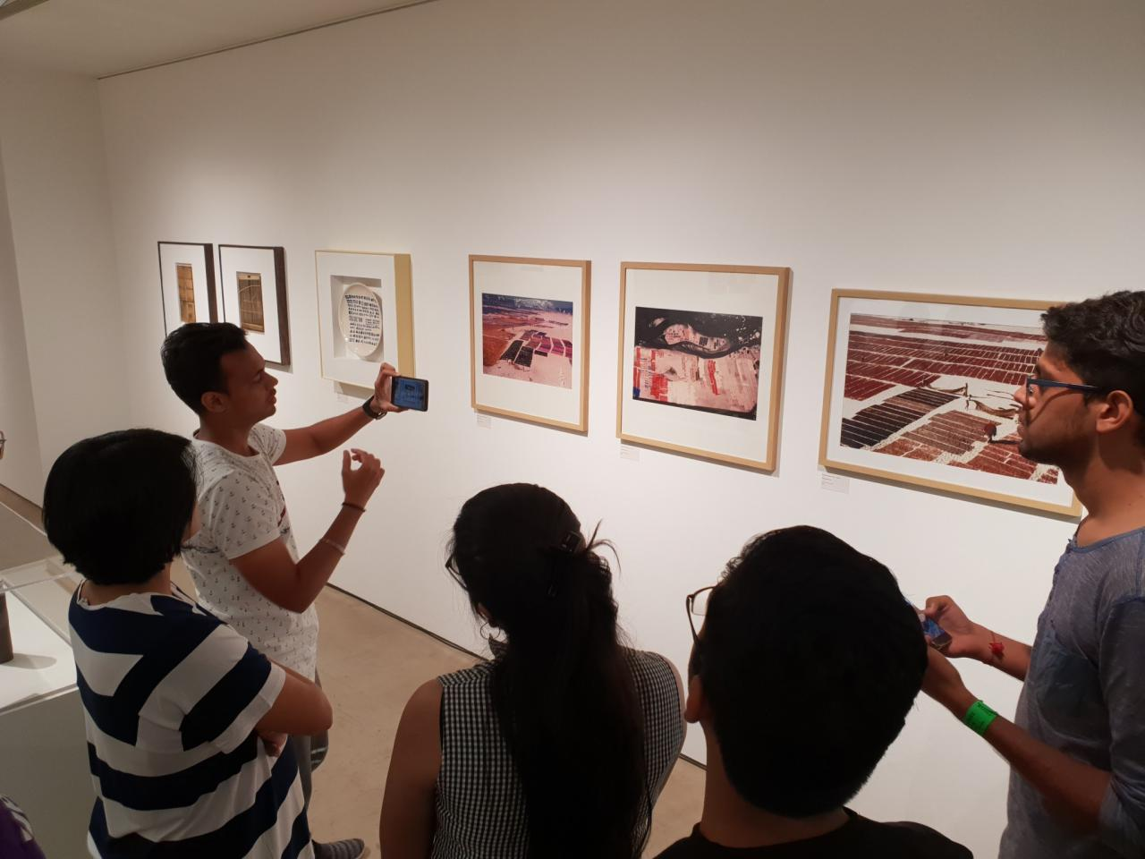 A group of young people looking at art hanging on the wall.