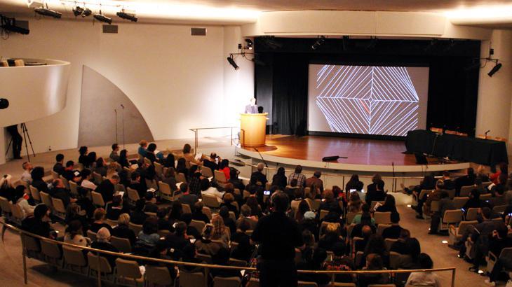 Ein Mann spricht von eine Bühne zu einem Publikum