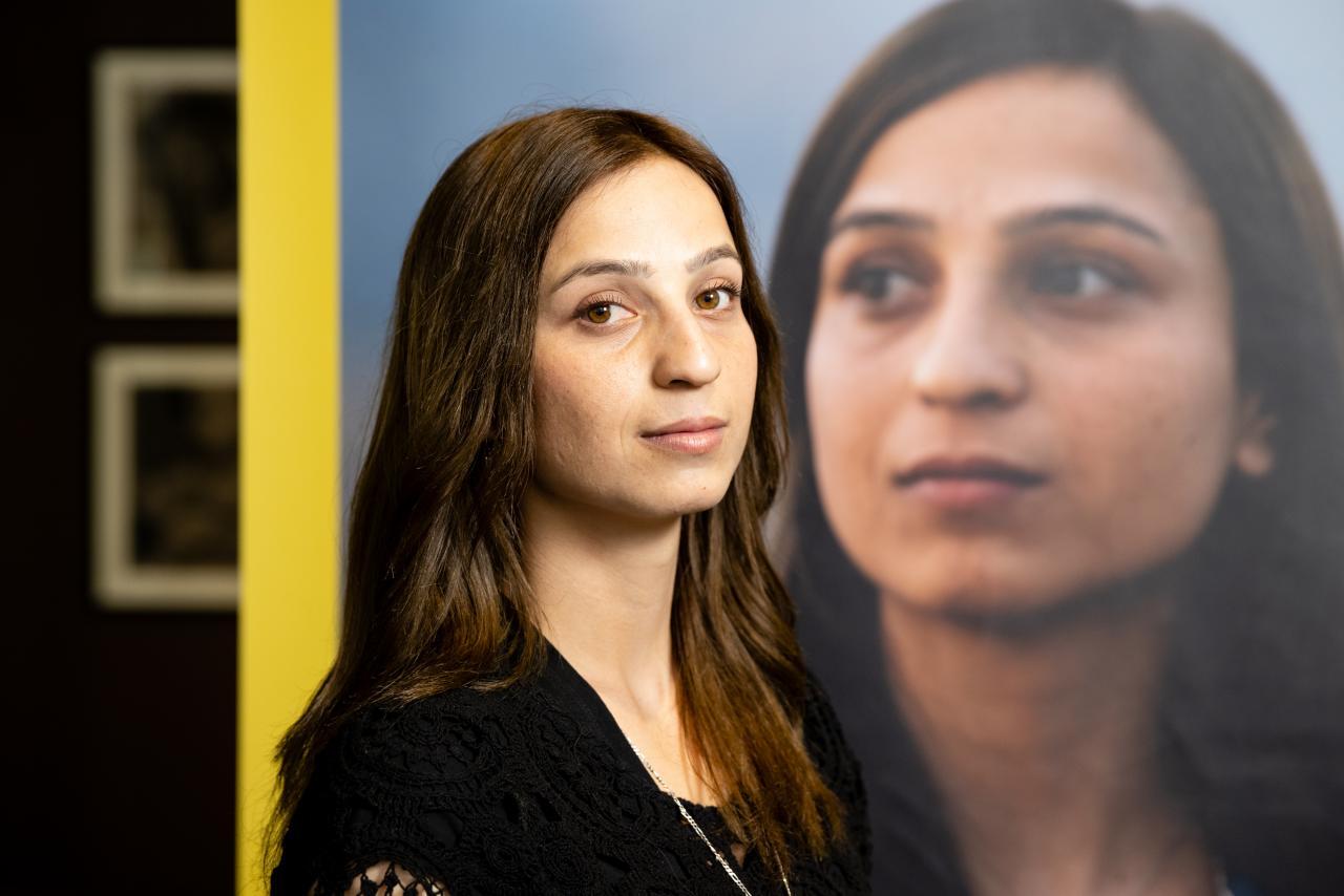 Zu sehen ist die jesidische Aktivistin Hala Safil vor dem Ausstellungsplakat