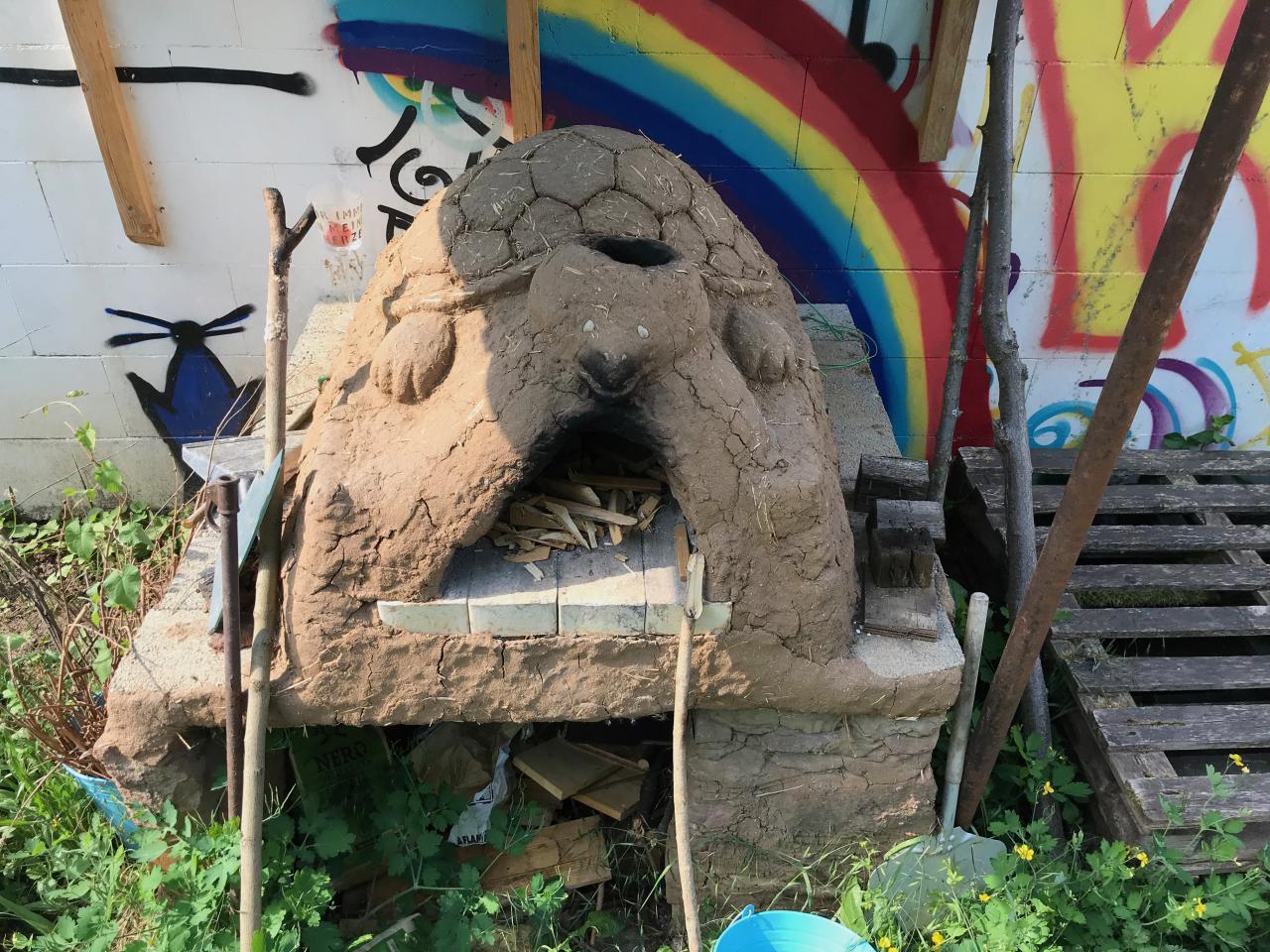 Eine Lehmofen mit einem aus Lehm gefertigten Schildkröte drauf.