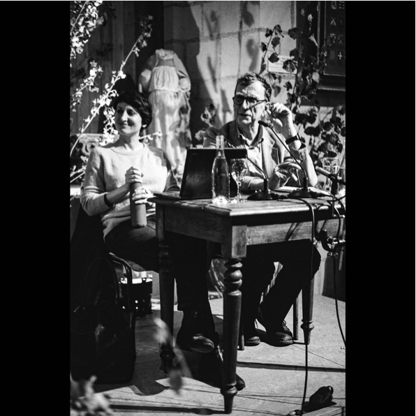 Bruno Latour und Frédérique Aït Touati sitzen nebeneinander an einem Tisch, sie wirken entspannt und zufrieden. Es scheint während einer Probe entstanden zu sein.