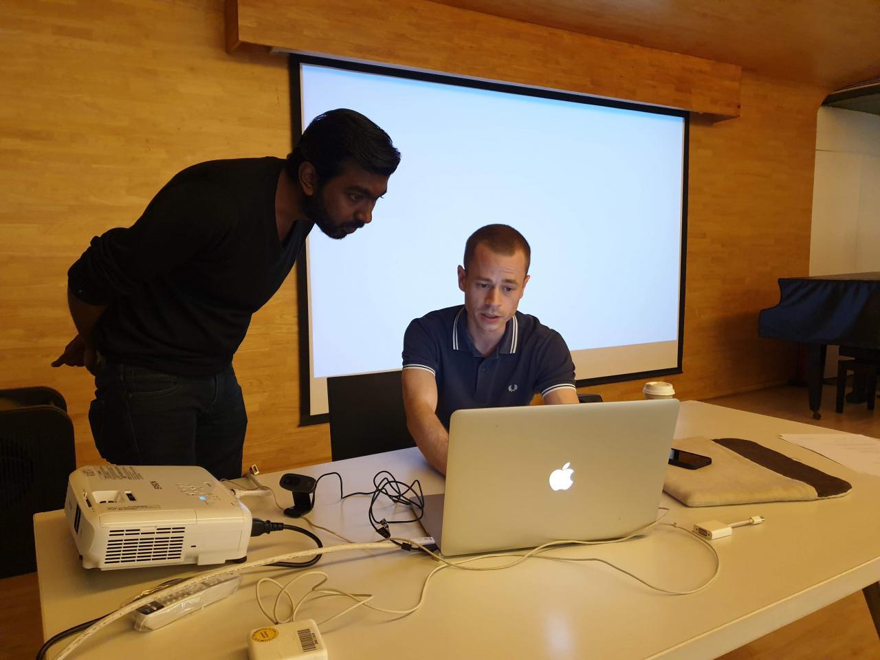 Zu sehen sind zwei Männer vor einem Laptop im Rahmen eines Workshops des ZKM im Goethe-Institut in Mumbai.
