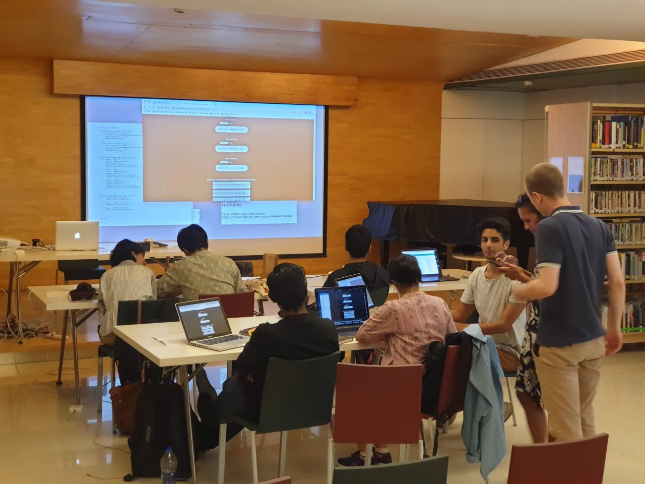 Zu sehen sind viele Menschen in einem Bibliotheksraum im Rahmen eines Workshops des ZKM im Goethe-Institut in Mumbai.