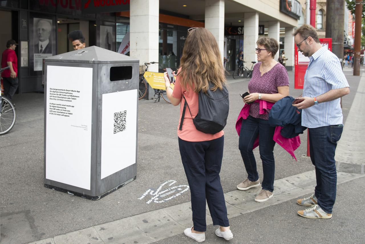 People with smartphones stand in front of a trash can with QR code