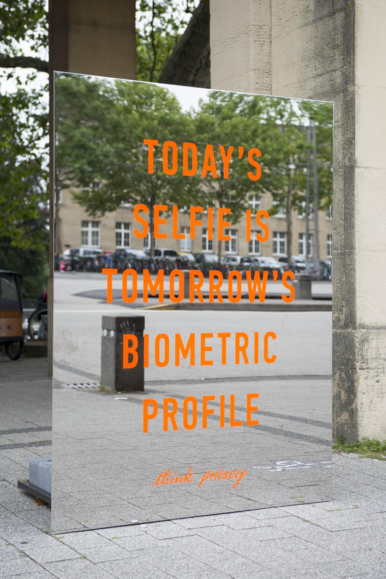 Zu sehen ist ein orangener Schriftzug »Todays Selfie is Tomorrows Biometric Profile« ist auf einem großen rechteckigen, rahmenlosen Spiegel. Die Installation steht draußen vor dem Eingang-Süd des Zoos.