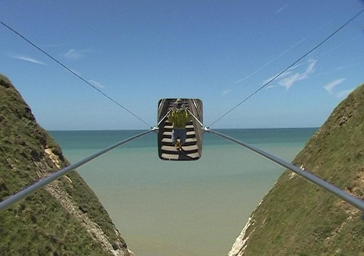 Links und rechts ragt jeweils ein bewaldeter Wels ins Bild. Zwischen teilen sich Meer und Himmel den Bildausschnitt. In der exakten Mitte des Bildes ist ein Spiegel an Drahtseilen aufgespannt, auf dem ein Mensch auf einer Steintreppe zu sehen ist.