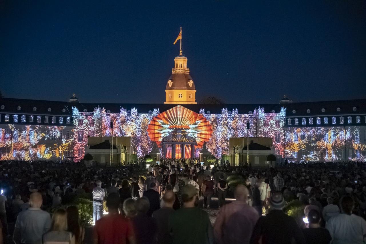 Auf der Fassade des Karlsruher Schlosses zeichnet sich eine riesige, digitale Muschel auf, die sich langsam öffnet. Um sie herum entsched ein buntes Farbenmeer.