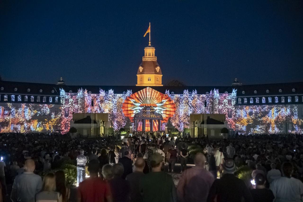 On the façade of Karlsruhe Castle, a huge digital shell emerges that slowly opens. A sea of colour surrounds it.