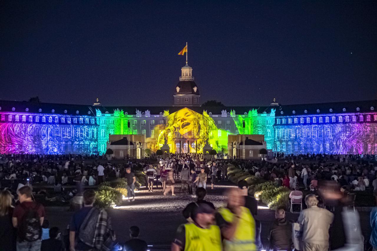 Fotografien des legendären Woodstock Fotografen Elliott Landy zeigen sich farbenfroh auf der Fassade des Karlsruher Schlosses.