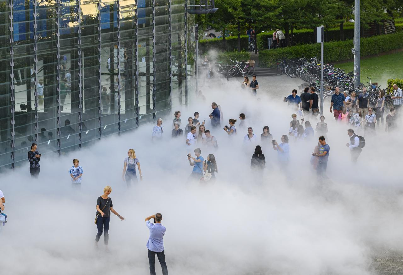 Das Foto zeigt einen Ausschnitt des Glaskubus des ZKMs vor deren vorderer rechten Ecke mehrere BesucherInnen in  der Nebelskulptur stehen und Fotos machen.