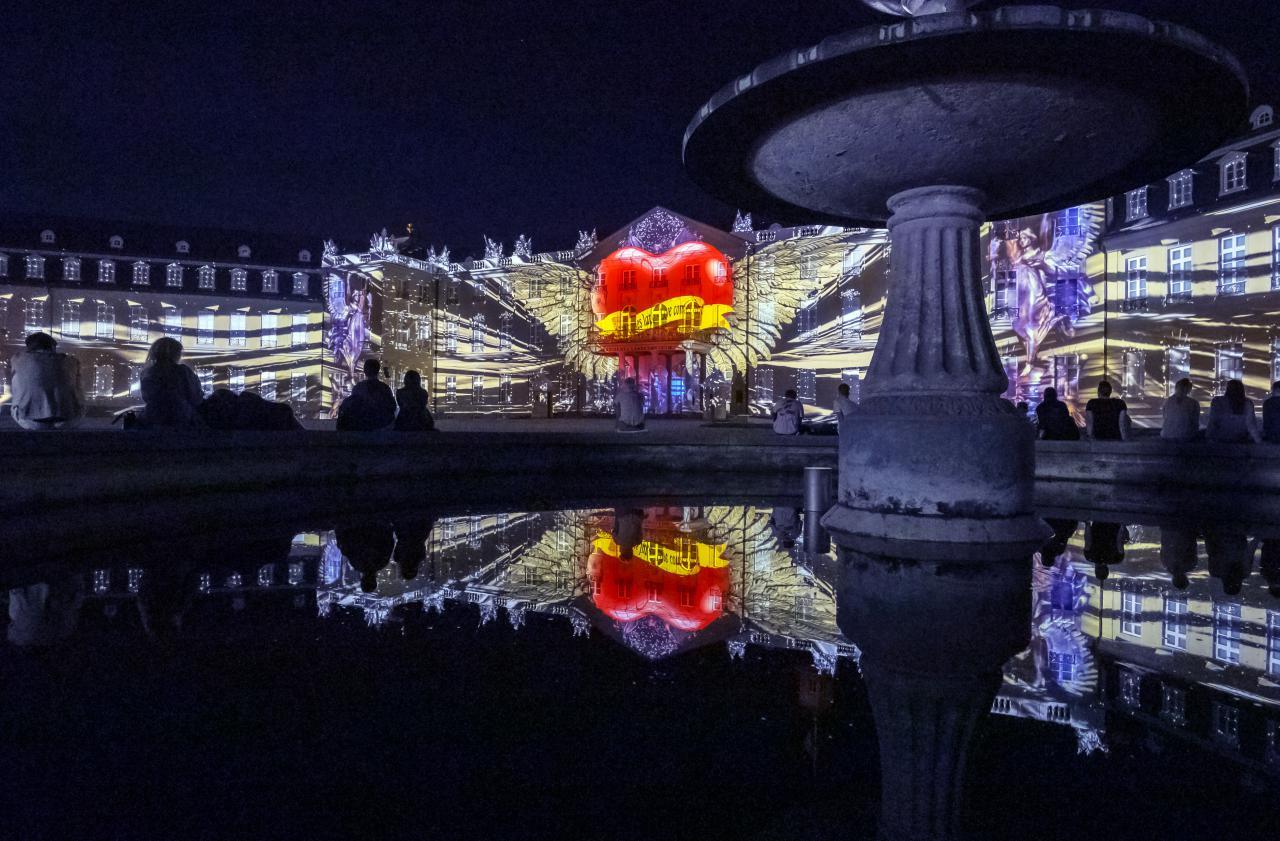Frei nach dem Motto »Love First« pulsiert ein großes rotes Herz mit Flügeln und Aufschrift auf der Fassade des Karlsruher Schlosses.
