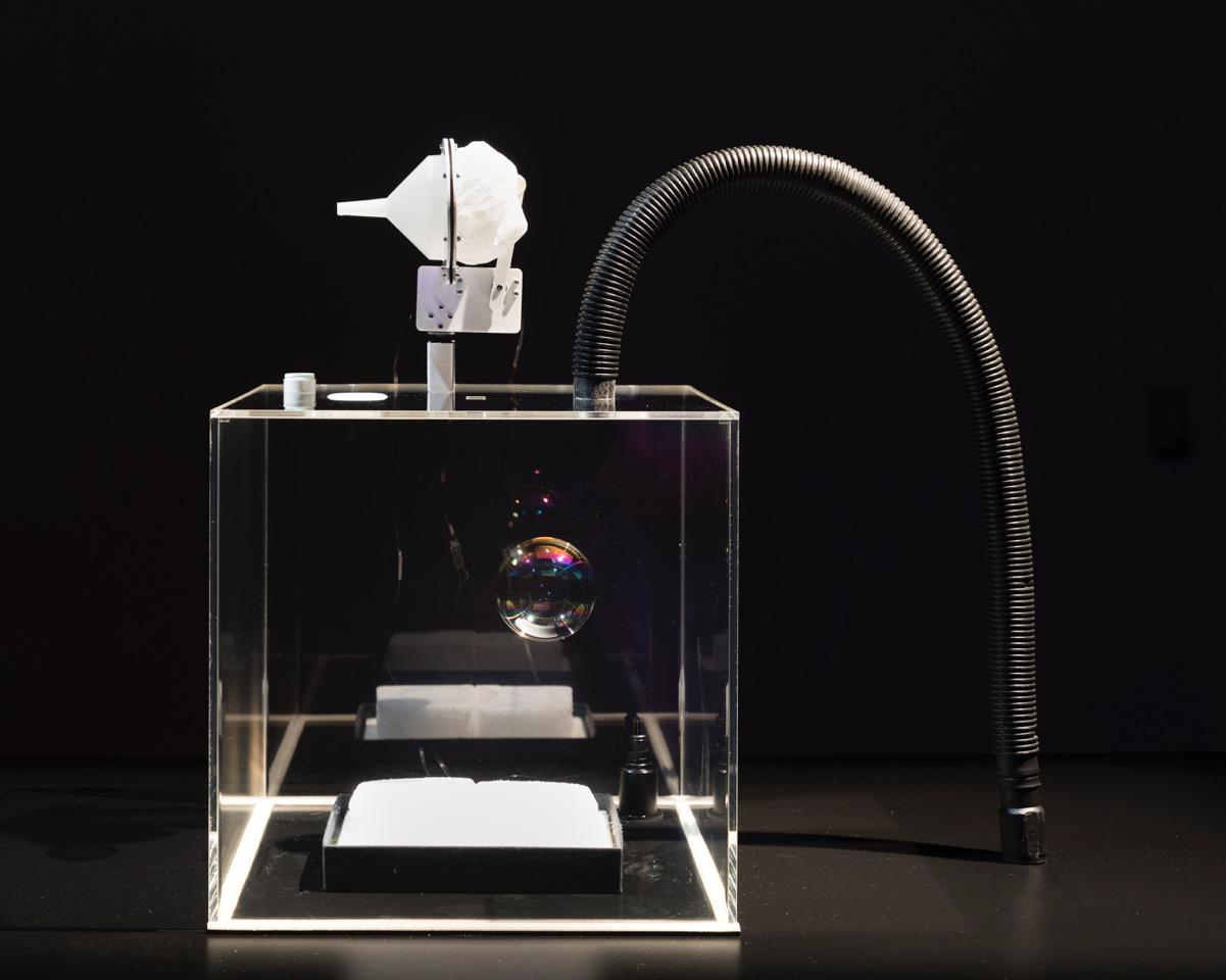 A vacuum cleaner tube opens into a square glass cuboid on which an installation is mounted.