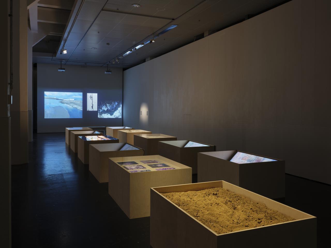 Zu sehen sind große Vitrinen vor einer weißen Wand. In den Vitrinen sind Bildschirme mit Videos und Fotos zu sehen.