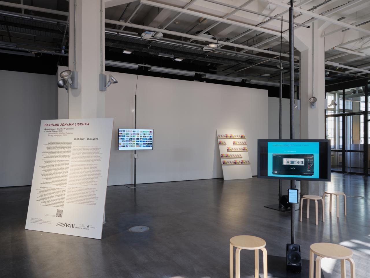 Blick in die Ausstellung. Zu sehen sind eine große Schrifttafel und zwei im Raum stehende Bildschirme. Vier Stühle stehen im Raum verteilt.