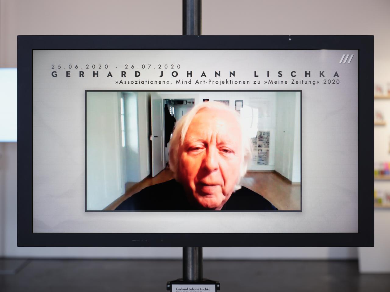 Zu sehen ist ein Bildschirm, auf dem das Gesicht eines alten Mannes spielt. Über dem Kopf des Mannes steht der Name Gerhard Johann Lischka.