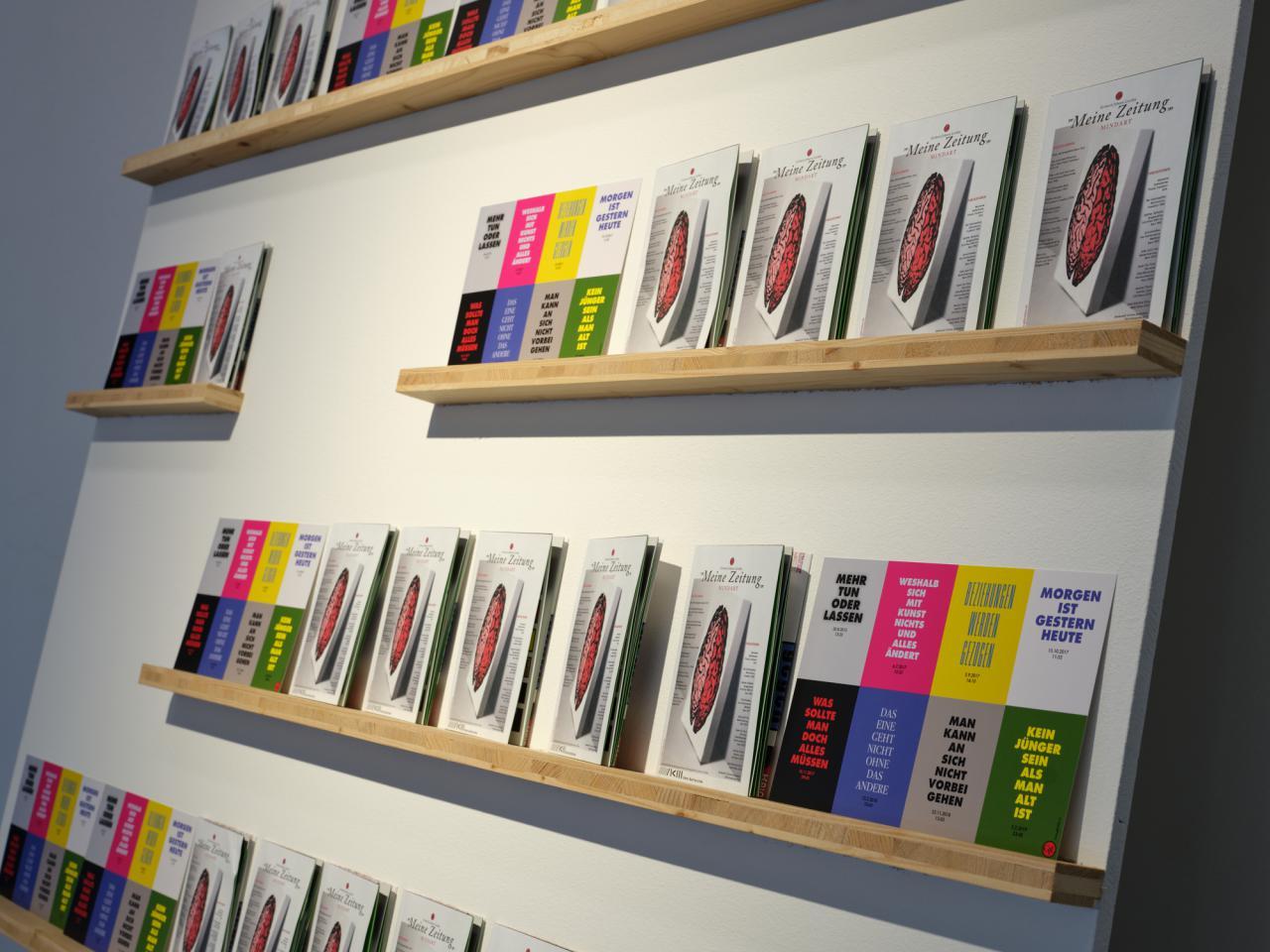 Zu sehen ist eine Wand, an welcher fünf Regale aus einzelnen Bretter befestigt wurden. Auf jedem der Regale stehen Flyer der Ausstellung.