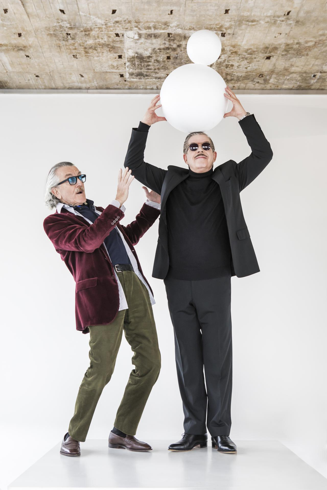 The musician duo Yello stands side by side in front of a wall. The one on the right wears a suit and holds a sculpture of two round balls above his head. The left one stands next to him in an intercepting position.